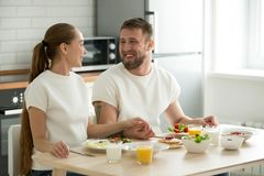 Happy young couple enjoying having breakfast at home kitchen tab. Happy young couple holding hands having breakfast cooked at home sitting at kitchen dining Stock Image