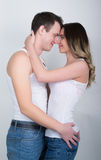 Happy young couple enjoying an intimate moment, laughing a lot and man gently strokes his partner's hair Stock Photos