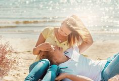 Happy young couple enjoying picnic on the beach and have good ti stock photography
