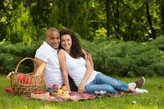 Happy young couple enjoying picnic in a park Stock Photo