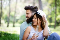 Happy young couple enjoying a picnic in the park together royalty free stock images