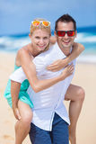 Happy young couple enjoying a solitary beach backriding. Happy couple piggybacking on beach during summer holidays vacation Royalty Free Stock Images