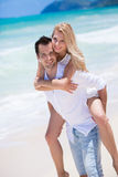 Happy young couple enjoying a solitary beach backriding. Happy couple piggybacking on beach during summer holidays vacation Stock Image