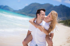 Happy young couple enjoying a solitary beach backriding. Happy couple piggybacking on beach during summer holidays vacation Stock Photography