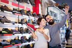 Happy young couple examining various shoes in shop royalty free stock photography