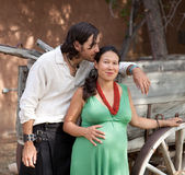 Happy young couple expecting a baby. Posing by an old wagon Royalty Free Stock Photos