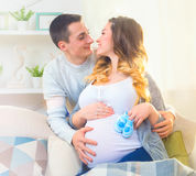 Happy young couple expecting baby. Beautiful pregnant women and her husband together caressing her pregnant belly Stock Photos