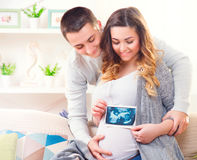 Happy young couple expecting baby. Beautiful pregnant women and her husband together holding ultrasound picture of their baby Stock Photo