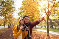 Happy young couple exploring in autumn at the park stock photo