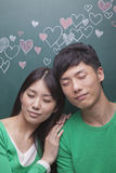 Happy young couple with eyes closed in front of blackboard with hearts Stock Image