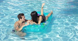 Happy young couple floating on mattress in pool. Happy young adult couple floating together on inflatable floating plastic mattress in outdoor pool stock video