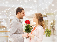 Happy young couple with flowers in mall. Relations, love, romance and people concept - happy young couple with flowers talking in mall with snow effect Stock Photos