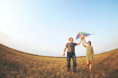 Happy young couple with flying a kite stock images