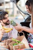 Playful young couple loading grocery bags into a car stock photos