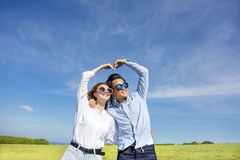 Happy  young  couple forming love shape Stock Image