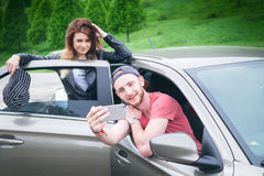 Happy young couple, friends making selfie while sitting in car. Summer time. Caucasian people. Concept of transportation. Stock Images