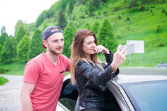 Happy young couple, friends making selfie while sitting in car. Summer time. Caucasian people. Concept of transportation. Stock Photo