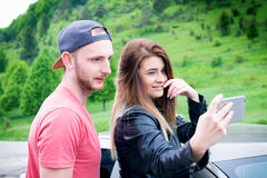 Happy young couple, friends making selfie while sitting in car. Summer time. Caucasian people. Concept of transportation. Stock Photography