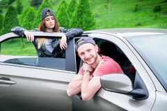 Happy young couple, friends making selfie while sitting in car. Summer time. Caucasian people. Concept of transportation. Royalty Free Stock Image