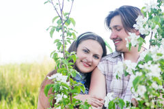 Happy Young Couple in garden of flowers Stock Image