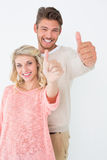 Happy young couple gesturing thumbs up Royalty Free Stock Image