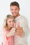 Happy young couple gesturing thumbs up Royalty Free Stock Photos