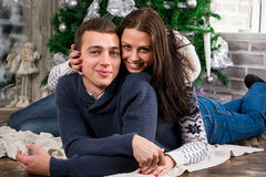 Happy young couple give each other gifts by the fireplace near t Stock Photography