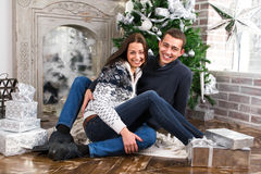 Happy young couple give each other gifts by the fireplace near t Royalty Free Stock Photography