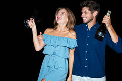 Happy young couple with glasses and bottle of champagne. On the beach at night royalty free stock photo