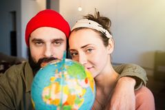 Happy young couple with globe choosing place for summer travel. Family travel concept. Happy young couple with globe choosing place for summer travel. Family royalty free stock image