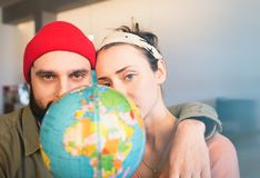 Happy young couple with globe choosing place for summer vacation at leisure. Family travel concept. Happy young couple with globe choosing place for summer royalty free stock photos