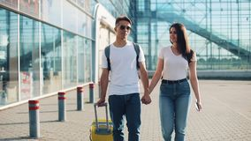 Happy young couple goes with luggage near the airport or railway station. The concept of travel, vacations, holidays. Summer time, sunset stock video