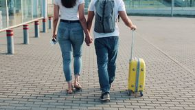 Happy young couple goes with luggage near the airport or railway station. The concept of travel, vacations, holidays. Summer time, sunset stock video footage