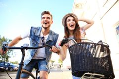 Happy young couple going for a bike ride on a summer day in the city.They are having fun together. Couple in love. Happy young couple going for a bike ride on a stock images
