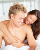 Happy young couple in a good mood on bed Royalty Free Stock Image