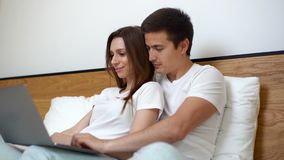 Happy young couple of guy and girl is lying in bed and watching film on laptop stock video footage
