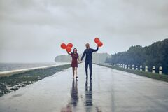 Happy young couple guy and girl are walking in the rain with bubble balls. hello concept autumn, good mood