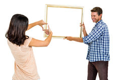 Happy young couple hanging picture frame Royalty Free Stock Image