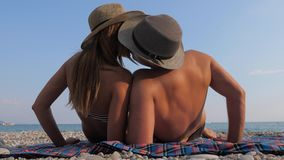 Happy Young Couple Sunbathing On The Beach, Lying On Her Back And Kisses. Happy young couple in the hat, sunbathing on the beach with a pebbly coastline, lying stock video