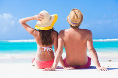 Happy young couple in hats sitting on a tropical Stock Photos