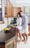 Happy young couple have fun in modern kitchen Stock Photos
