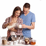 Happy young couple have fun in modern wooden kitchen indoor while preparing fresh food.  stock image