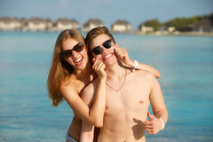 Happy young couple have fun and relax on the beach. Woman makes man smile holding cheeks with hands. Bungalows of spa Stock Photography