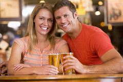 Happy young couple having beers at a bar Royalty Free Stock Images