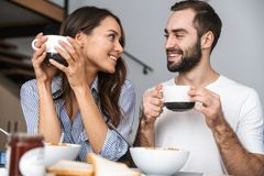 Happy young couple having breakfast royalty free stock image