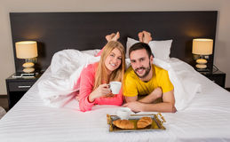 Happy young couple having breakfast tray on bed at home Stock Photos
