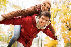 Happy young couple having fun in autumn park Stock Photos