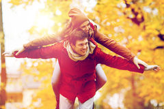 Happy young couple having fun in autumn park Royalty Free Stock Photos