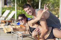 Happy young couple having fun  on the beach. Happy young couple on summer vacation smiling and hugging Stock Photos