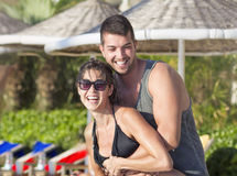 Happy young couple having fun  on the beach. Happy young couple on summer vacation smiling and hugging Stock Photography